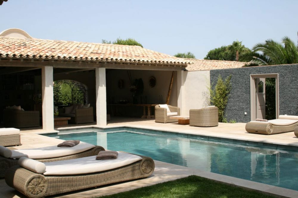 Aménagement d'un ensemble extérieur : terrasse et abord de piscine en pierre beige