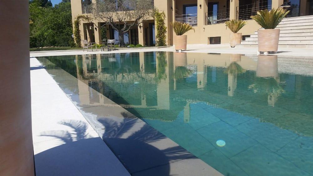 Piscine en pierre naturelle, margelle en pierre beige Cèdre Gray et fond de piscine en pierre grise-taupe Forest Grey