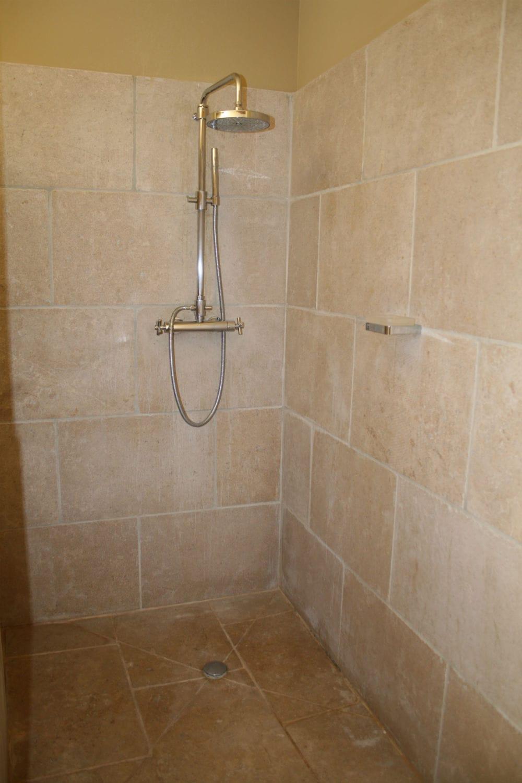 Parement mural en pierre beige et sol de douche en pierre