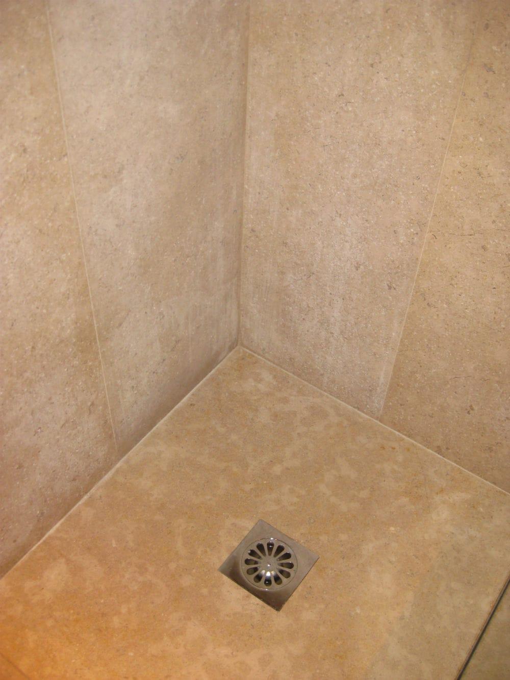 Ensemble de douche en pierre : receveur et carrelage mural.